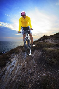 young man riding moutain bike mtb on land dune against dusky sky