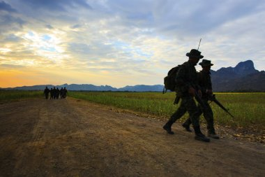 Silhouette motion of long range patrolling soldier walking on di