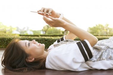 young beautiful woman lying on home terrace and playing smart ph