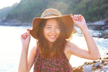 portrait face of beautiful woman wearing wide straw hat standing