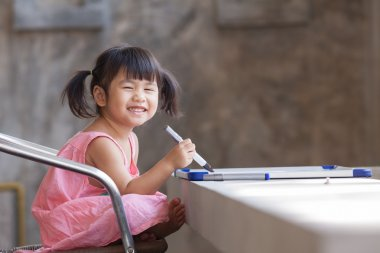 lovely face of toothy smiling asian children practive to writing