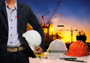 Engineer man with white safety helmet standing against working