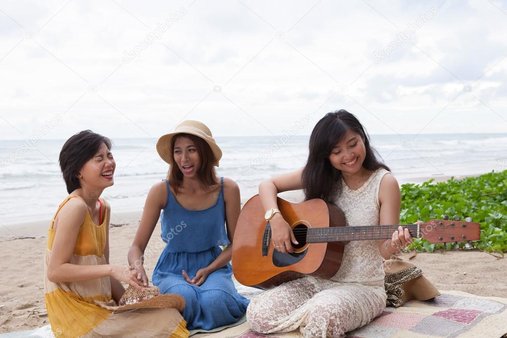 portrait group of young asian woman playing guitar in sea beach