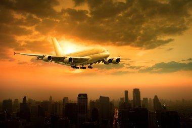 passenger jet plane flying over urban scene against beautiful su