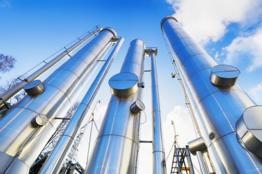 Large oil and gas pipes against clear blue sky