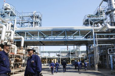 Refinery workers inside large oil industry plant
