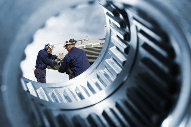 Engineers, workers seen through giant cogwheels