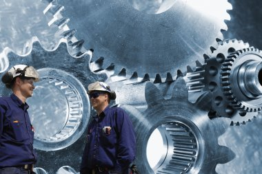 Engineers seen through a giant gear axle