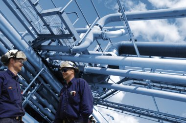 oil and gas workers with refinery pipelines