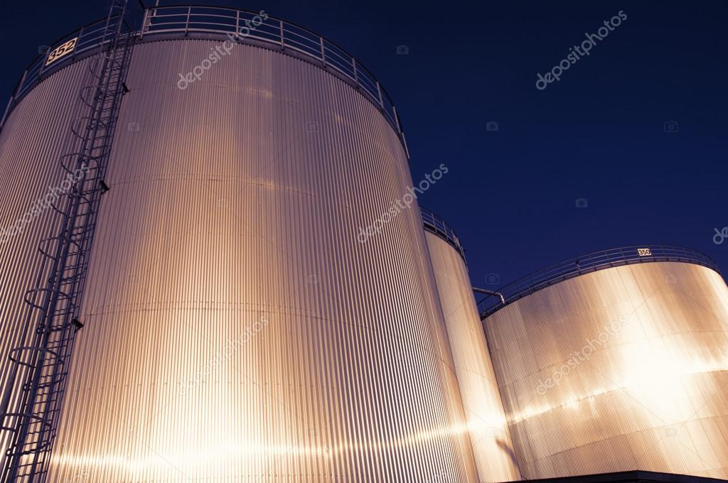 large oil and fuel tanks at sunset