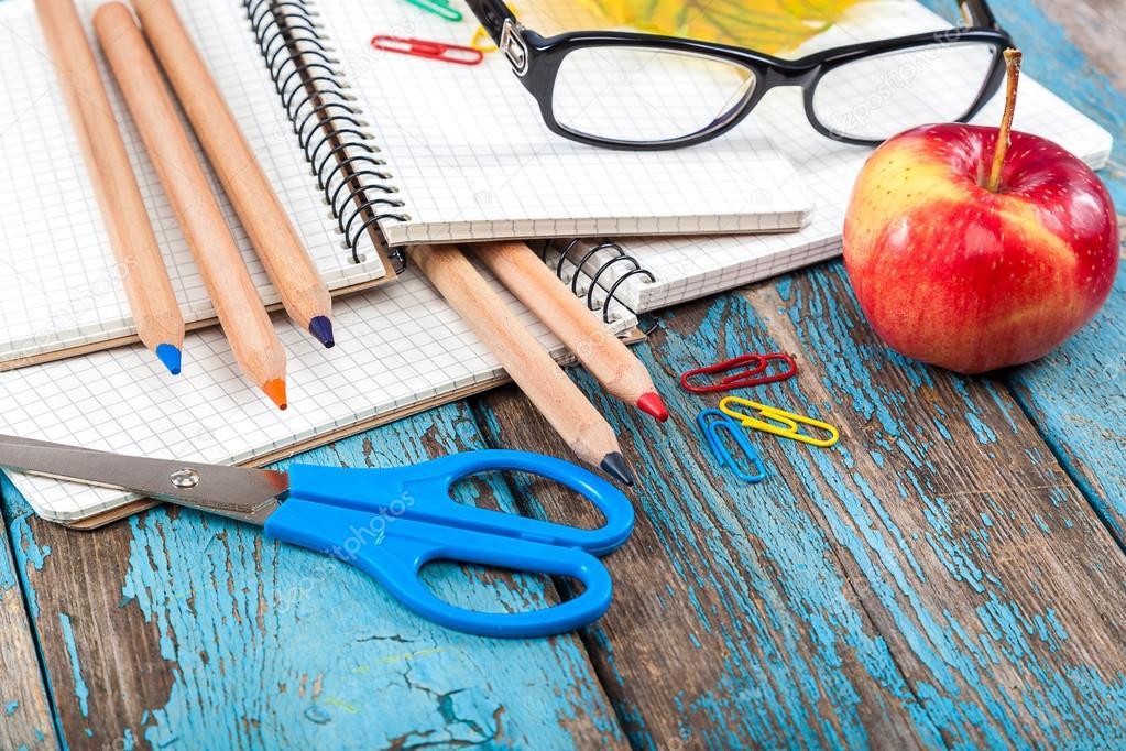 Office or school supplies on wooden planks.