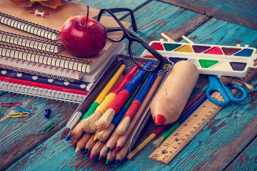 Office or school supplies on wooden planks painted in blue.