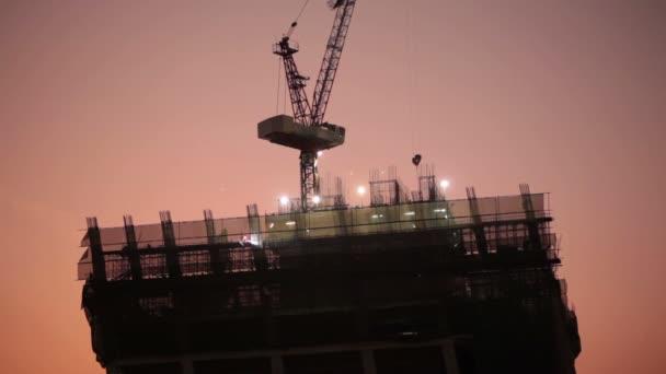 stavební dělník v průmyslu místě, stavební vývoj pro mrakodrap, na západ slunce scéna, nízký úhel pohledu