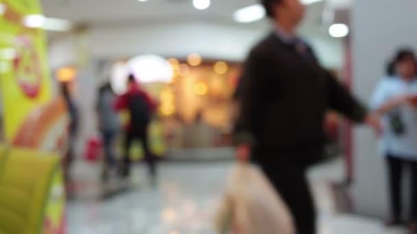 abstraktní rozostření pozadí nákupního střediska a dav pěších lidí používá eskalátor v nákupním středisku s bokehem