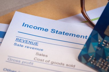 Income statement letter on brown envelope and eyeglass, business