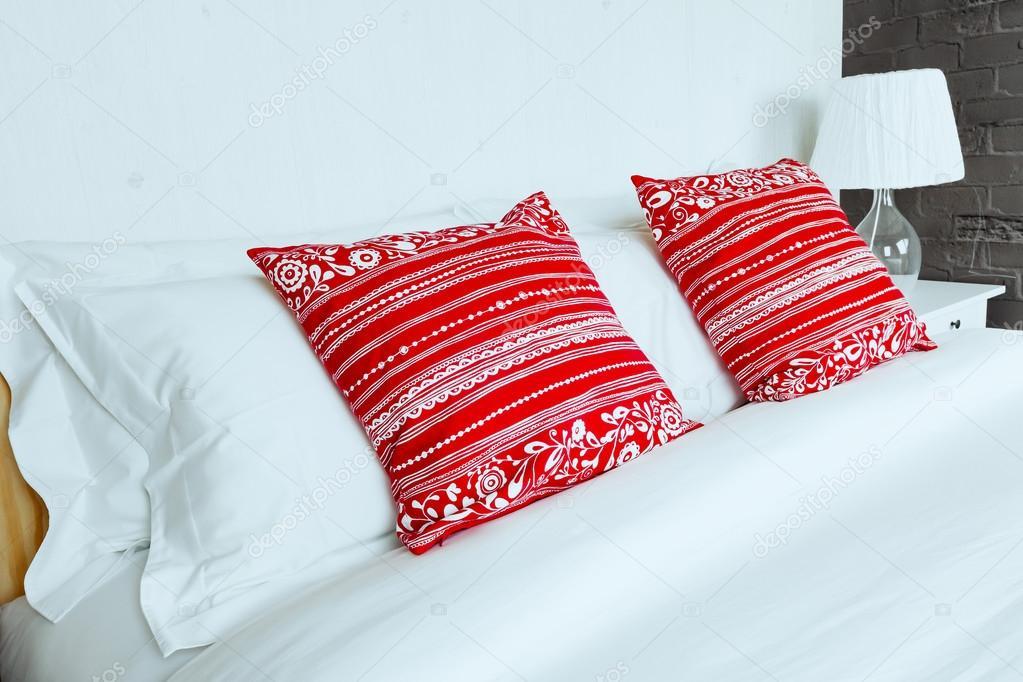 Rode Slaapkamer Accessoires : Rode kussen op slaapkamer met witte bed blad en lamp u stockfoto