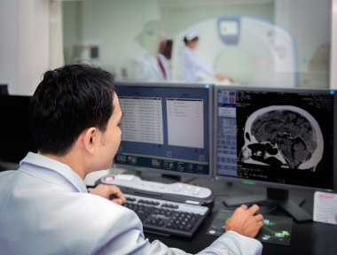 Medical team operating computers in CT scan lab