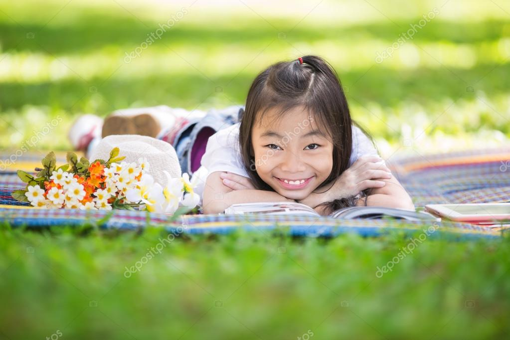 Funny little Asian girl reading and learning with tablet pc