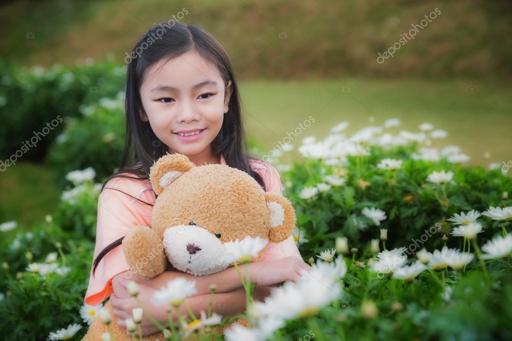 little girl with doll bear in nature park