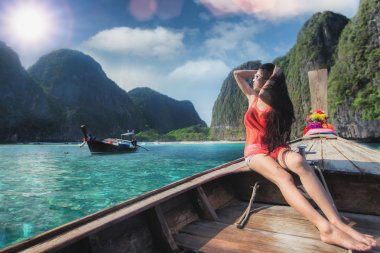Asian lady relax on long tail boat at maya beach