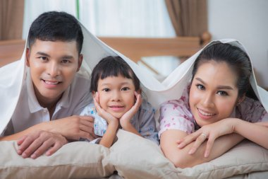Family in the duvet smiling on the bed
