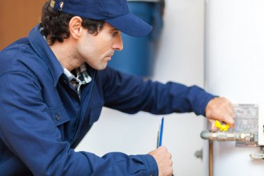 Plumber at work with hot-water heater