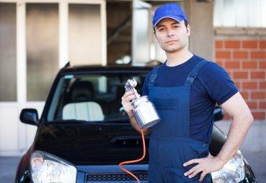 Car body repairer holding spray gun