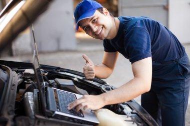 Mechanic using laptop computer