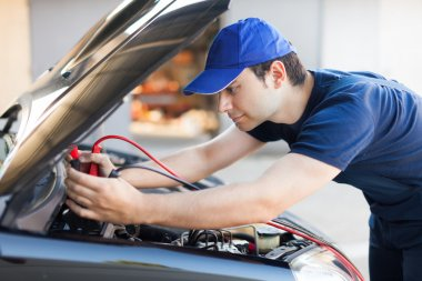 Mechanic using booster cables