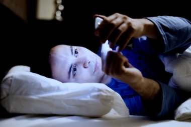 Man using mobile phone in bed