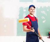freundlicher Maler bei der Arbeit in einer Wohnung