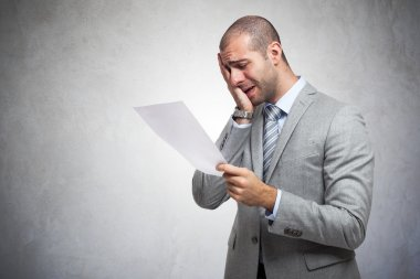 Depressed man reading document