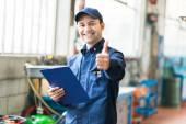Dělník v továrně ukazuje palec