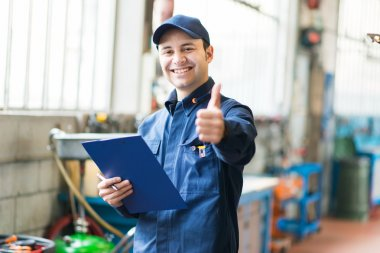 Worker in factory showing thumbs up