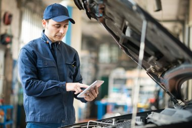 Mechanic using tablet in his garage