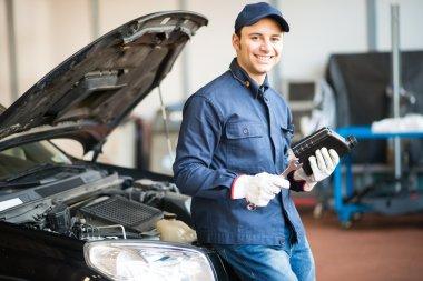 Mechanic holding jug of motor oil
