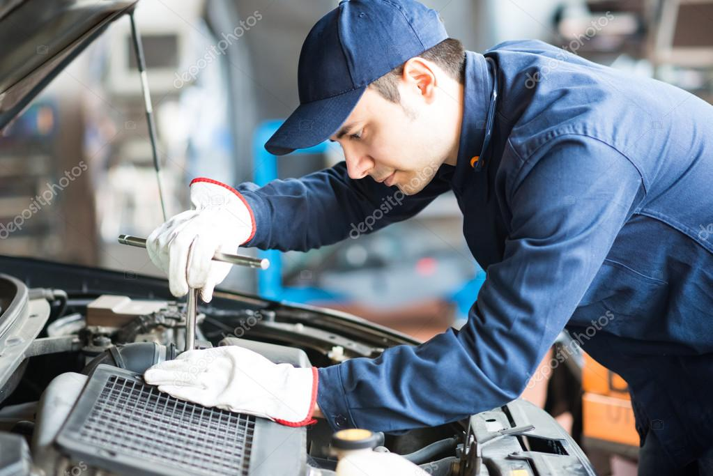 Mechanic working on car in garage