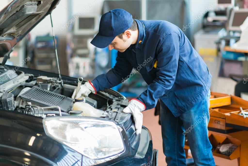 Mechanic at work on car in garage