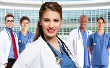 Smiling doctor in front of medical workers