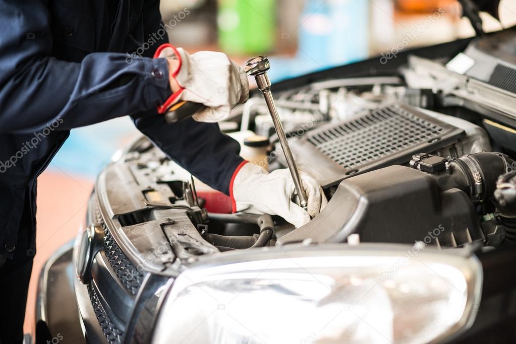 Auto mechanic at work on car in garage