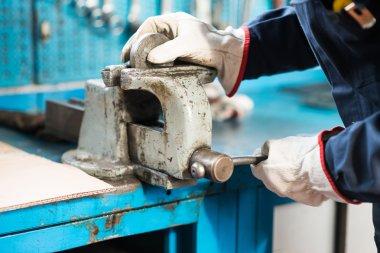 Worker securing metal plate in vise