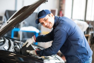 Auto mechanic putting oil in car