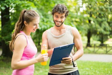 Man showing training table to woman