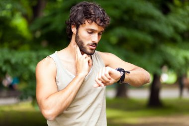 Male runner looking at sports smart watch