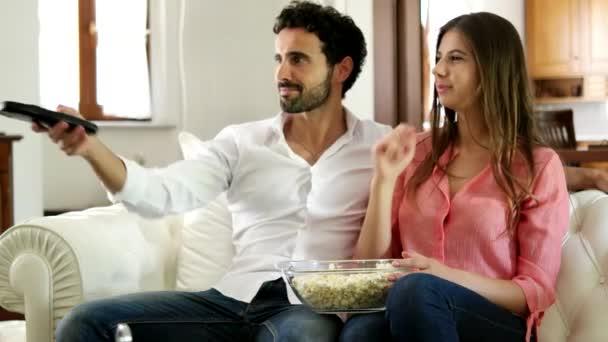 pár jíst popcorn při sledování televize