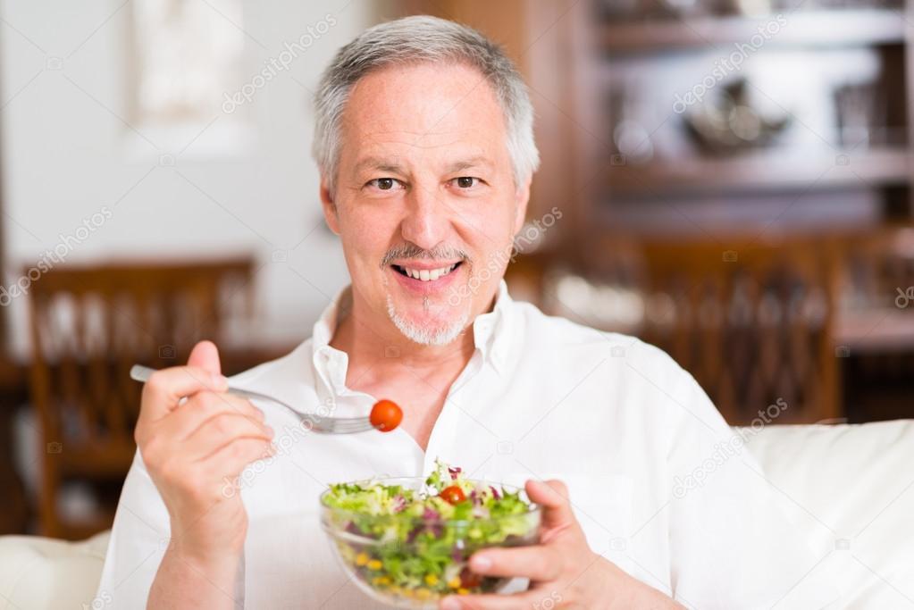 mature man eating a salad