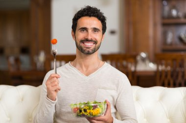 Portrait of a man eating a salad in his apartment stock vector
