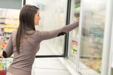 Woman taking deep food from freezer