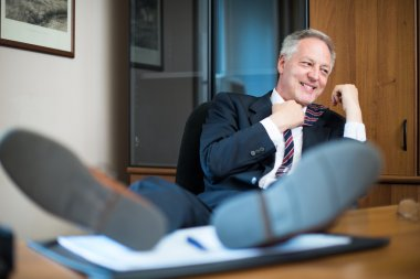 Mature man relaxing in his office