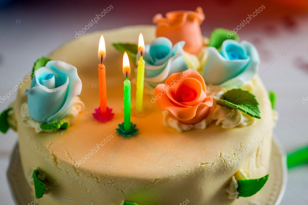 Beautiful birthday cake with lighted candles and marzipan roses